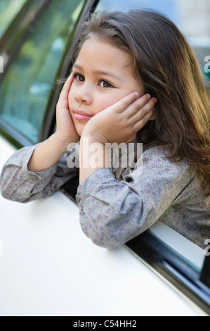 Cute little girl looking out of the car window - Stock Photo