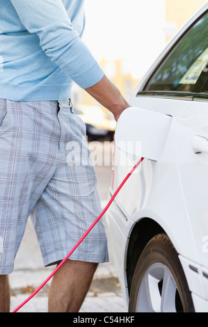 Mid section view of a mid adult man charging the electric car - Stock Photo