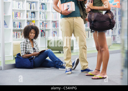Portrait of university student sitting on the floor with friends standing beside - Stock Photo