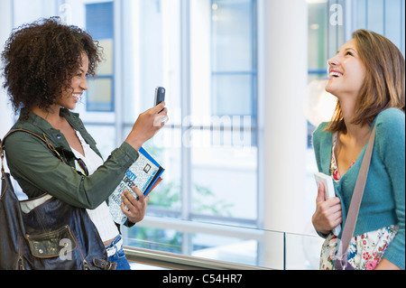 African American woman taking photos of her Caucasian friend - Stock Photo