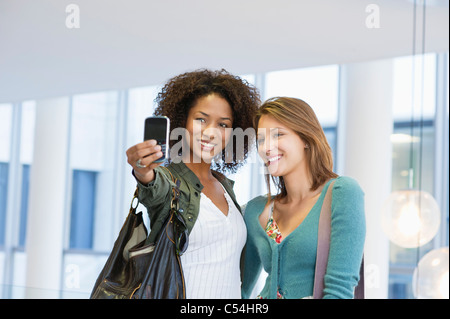 Two women taking photos of themselves - Stock Photo
