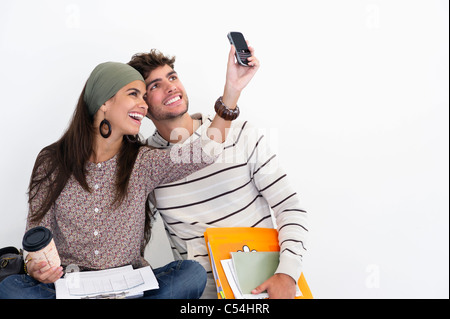 Two young friends taking photos of themselves against white background - Stock Photo