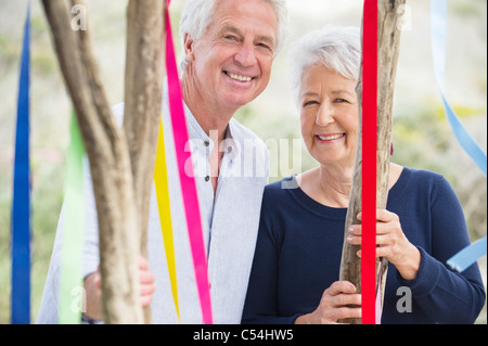 Portrait of a senior couple standing near a decorated tree - Stock Photo