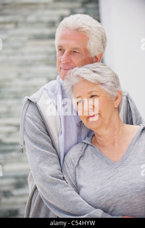 Senior man embracing his wife from behind - Stock Photo