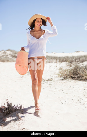 Young woman walking on the beach - Stock Photo
