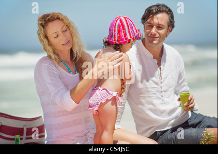 Mother applying suntan lotion to her daughter's back on the beach - Stock Photo