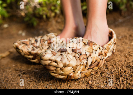 Low section view of a woman wearing wicker shoe - Stock Photo
