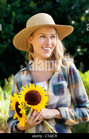 Happy young woman holding sunflowers in a field - Stock Photo