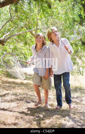 Little boys looking away in forest with net in hand - Stock Photo