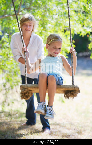 Smiling little siblings playing in tree swing - Stock Photo