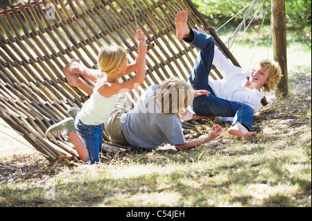 Little children falling down from hammock - Stock Photo