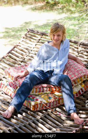 Smiling little boy looking away while sitting in hammock - Stock Photo