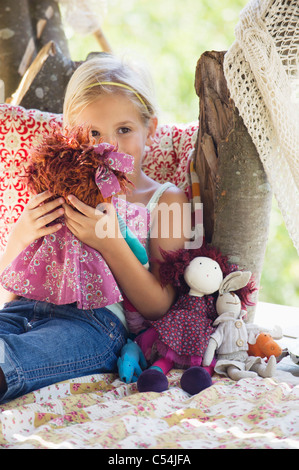Contemplative little girl holding toys in tree house - Stock Photo