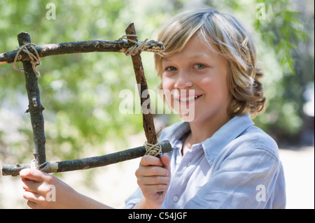 Portrait of a cute little boy holding frame of driftwood outdoors - Stock Photo