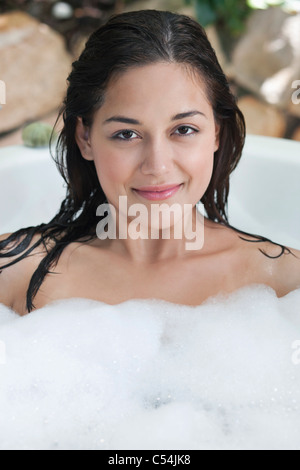 Portrait of a beautiful young woman taking bubble bath - Stock Photo