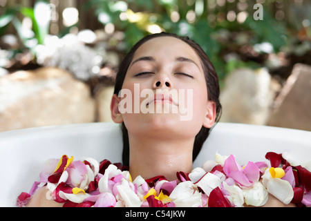 Beautiful young woman relaxing in bathtub with petals - Stock Photo