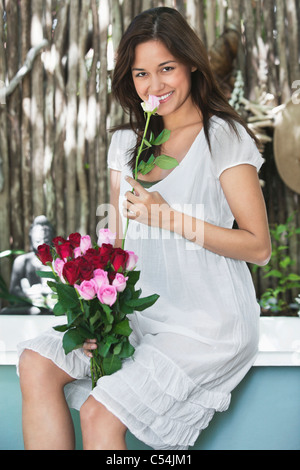 Portrait of a young woman smelling flower - Stock Photo