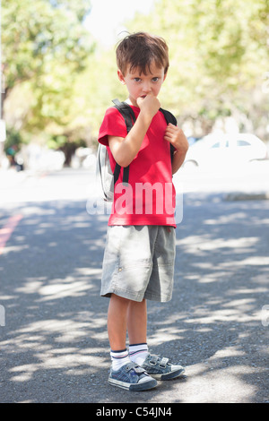 Portrait of a cute little boy standing with finger in mouth - Stock Photo