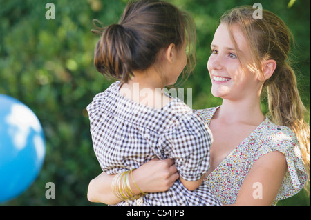 Cute girl carrying little sister and smiling - Stock Photo