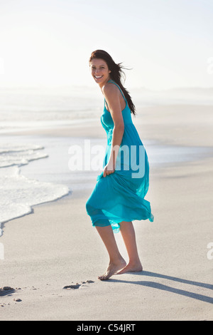 Cheerful young woman standing on a beach - Stock Photo