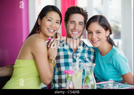 Women sitting with hand on a man's shoulders in restaurant - Stock Photo