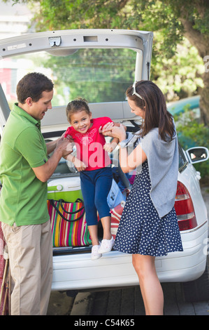 Smiling parents lifting little girl against car - Stock Photo