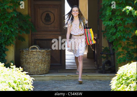Portrait of a little girl walking out of her home - Stock Photo
