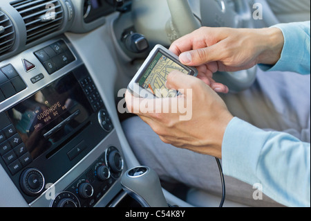 Close-up of human hand using GPS navigation system in car - Stock Photo