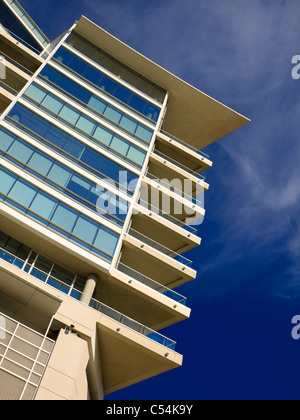 A high-end residential building with glass balconies shoot against a deep blue sky. - Stock Photo