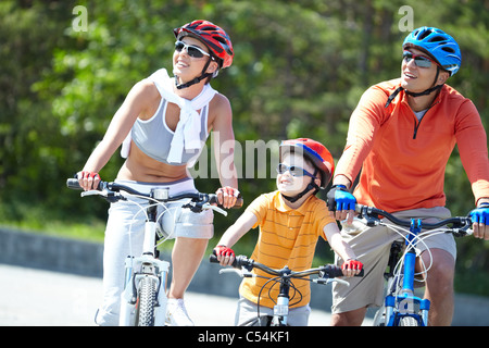 Portrait of happy family riding on bicycles at leisure - Stock Photo