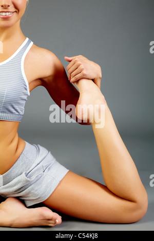 Image of female stretching leg during physical exercise in isolation - Stock Photo