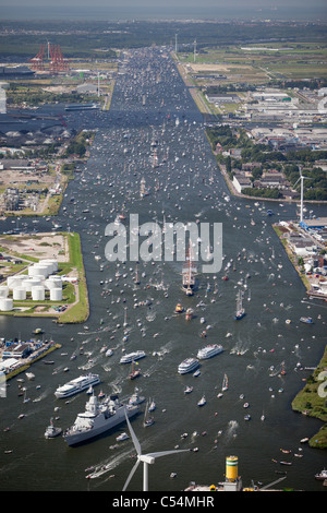 Aerial of parade of tall ships from IJmuiden to Amsterdam through canal called Noordzeekanaal. View on Amsterdam - Stock Photo