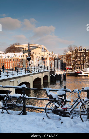 The Netherlands, Amsterdam, 17th century houses at river called Amstel. Background Skinny Bridge. Winter, snow. - Stock Photo