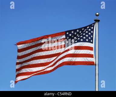 Close-up of American flag fluttering against blue sky - Stock Photo