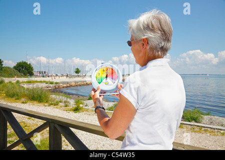 Woman measuring a high UV index in the afternoon sun on a portable sun UV station on the beach. - Stock Photo