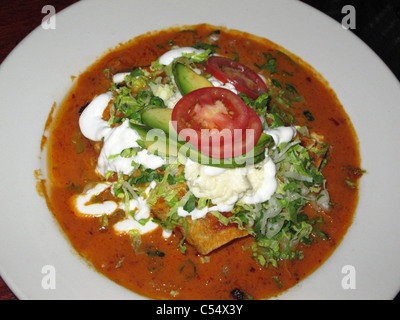 Mexican Food Enchiladas with Red Salsa, tomatoe, Guacamole and Avocado. Typical food from Mexico - Stock Photo