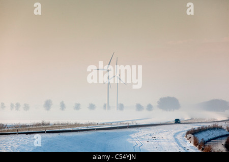 The Netherlands, Lelystad, Windturbines. Snow, winter. Car - Stock Photo
