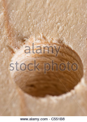 Hole drilled in plank of wood - Stock Photo