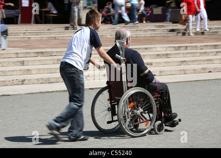 Old man in a wheelchair pushed by a boy, Berlin, Germany - Stock Photo