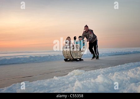The Netherlands, Hindeloopen, the Dutch capital of skating culture. Man on skates pushing antique sledge. Sunset. - Stock Photo