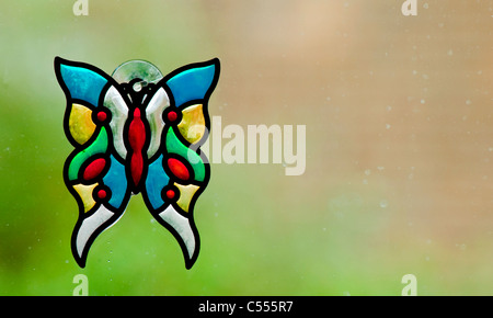 Stained glass butterfly on a rainy window - Stock Photo