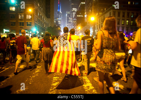 A spectator wearing an American flag leaves after viewing the 35th annual Macy's Fourth of July fireworks in New - Stock Photo