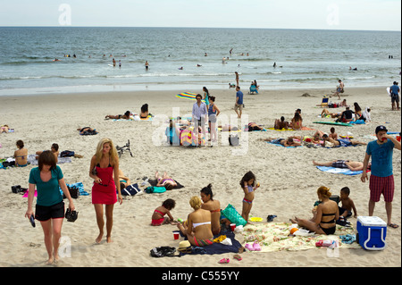 Beachgoers take advantage of the warm summer sun at Rockaway Beach in the Queens borough of New York - Stock Photo