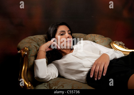 Serious woman lying on sofa - Stock Photo