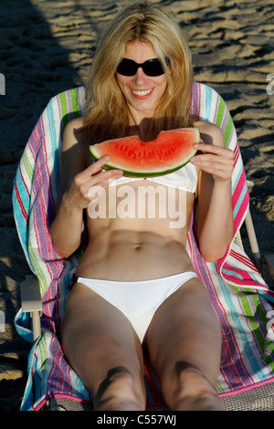 USA, New Jersey, Young woman eating watermelon on beach - Stock Photo