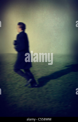 Blurred profile of a man running away - Stock Photo