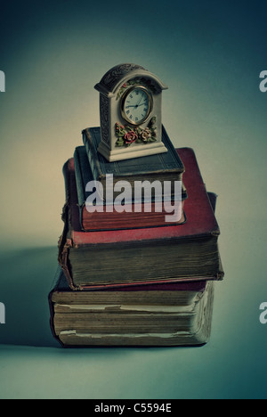 Old fashioned clock over a pile of books - Stock Photo