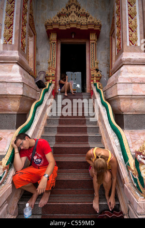 Tired European tourists resting at entrance to Wat Chalong - Buddhist temple in Phuket, Thailand. - Stock Photo