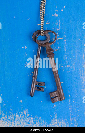 Two old keys hanging from a chain - Stock Photo