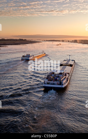 The Netherlands, Nijmegen, Cargo boats on Waal river. Sunrise. - Stock Photo